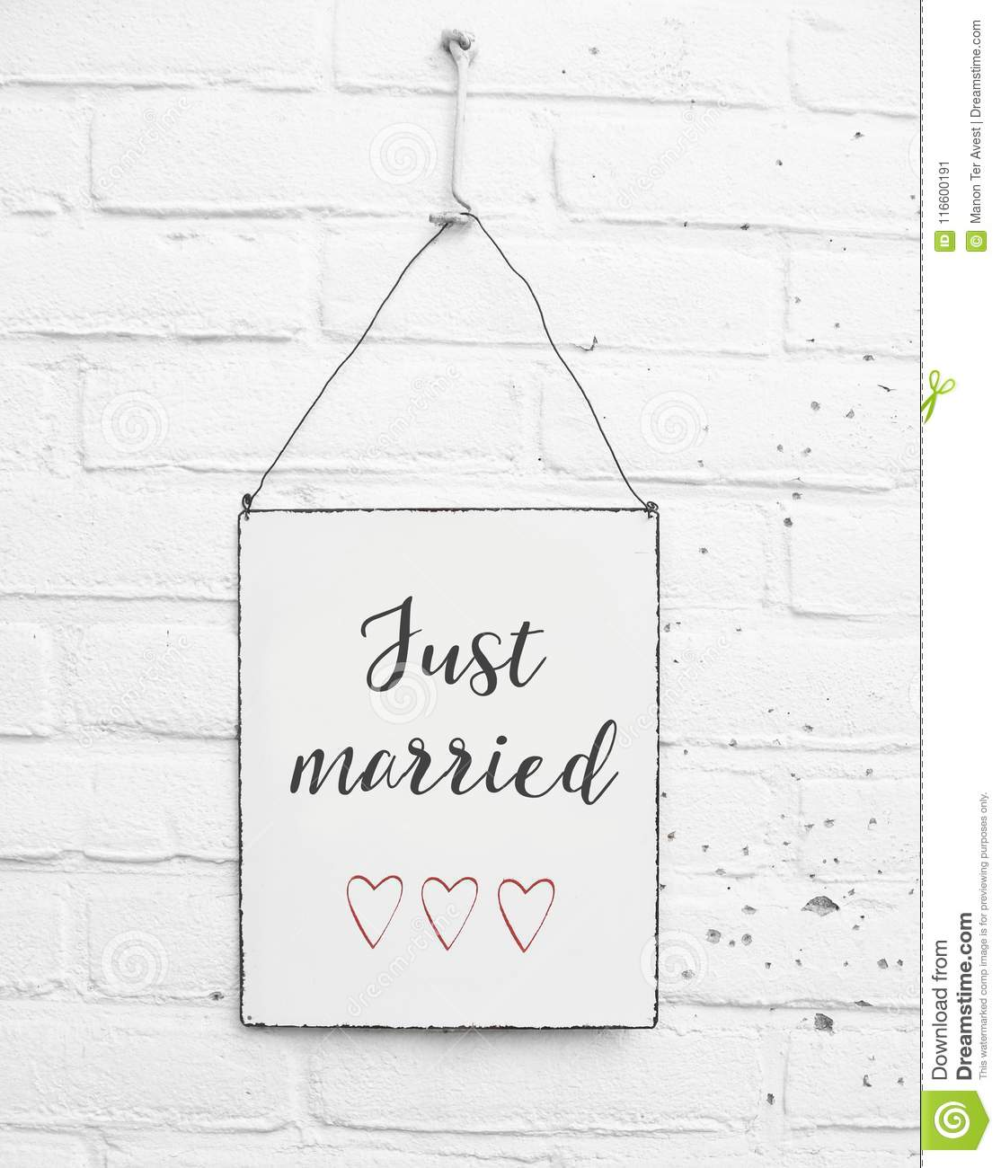 White square metal plate on white bricks background - with text just married for love couples and weddings