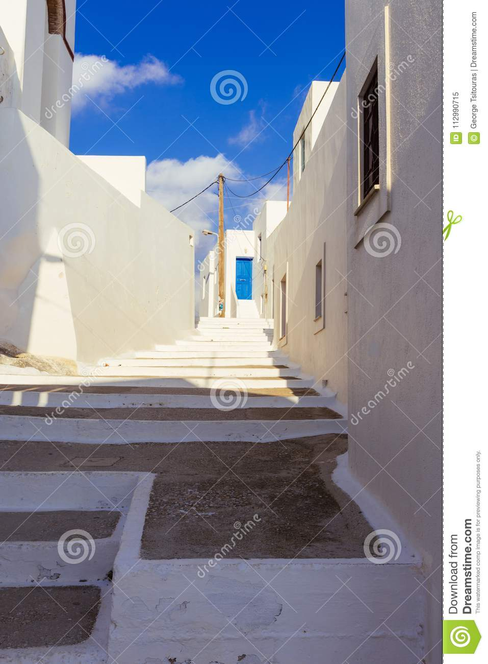 White stairs that lead to ablue door in the Lagada of Amorgos