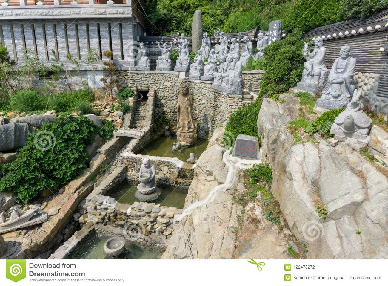 White stone carved statues of Chinese Buddha, priests and many animals on the artificial waterfall at Haedong Yonggungsa Temple