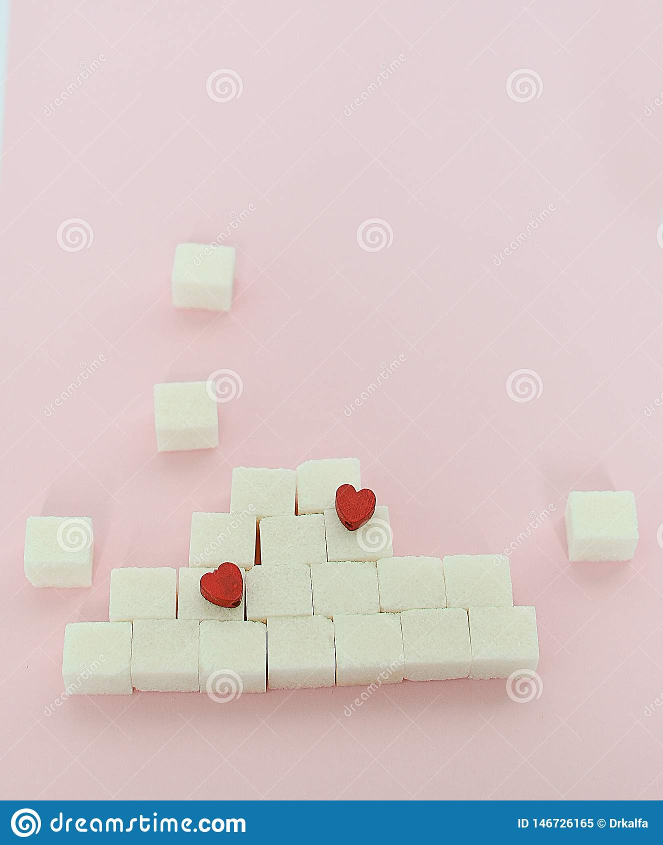 White sugar cubes on a pink background. What are the concepts of diabetes and calorie intake The concept of heart disease. No
