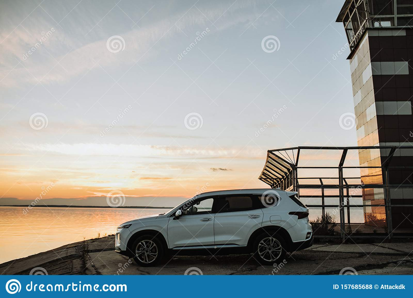 White compact SUV car with sport and modern design parked on concrete road by the sea near the beach at sunset