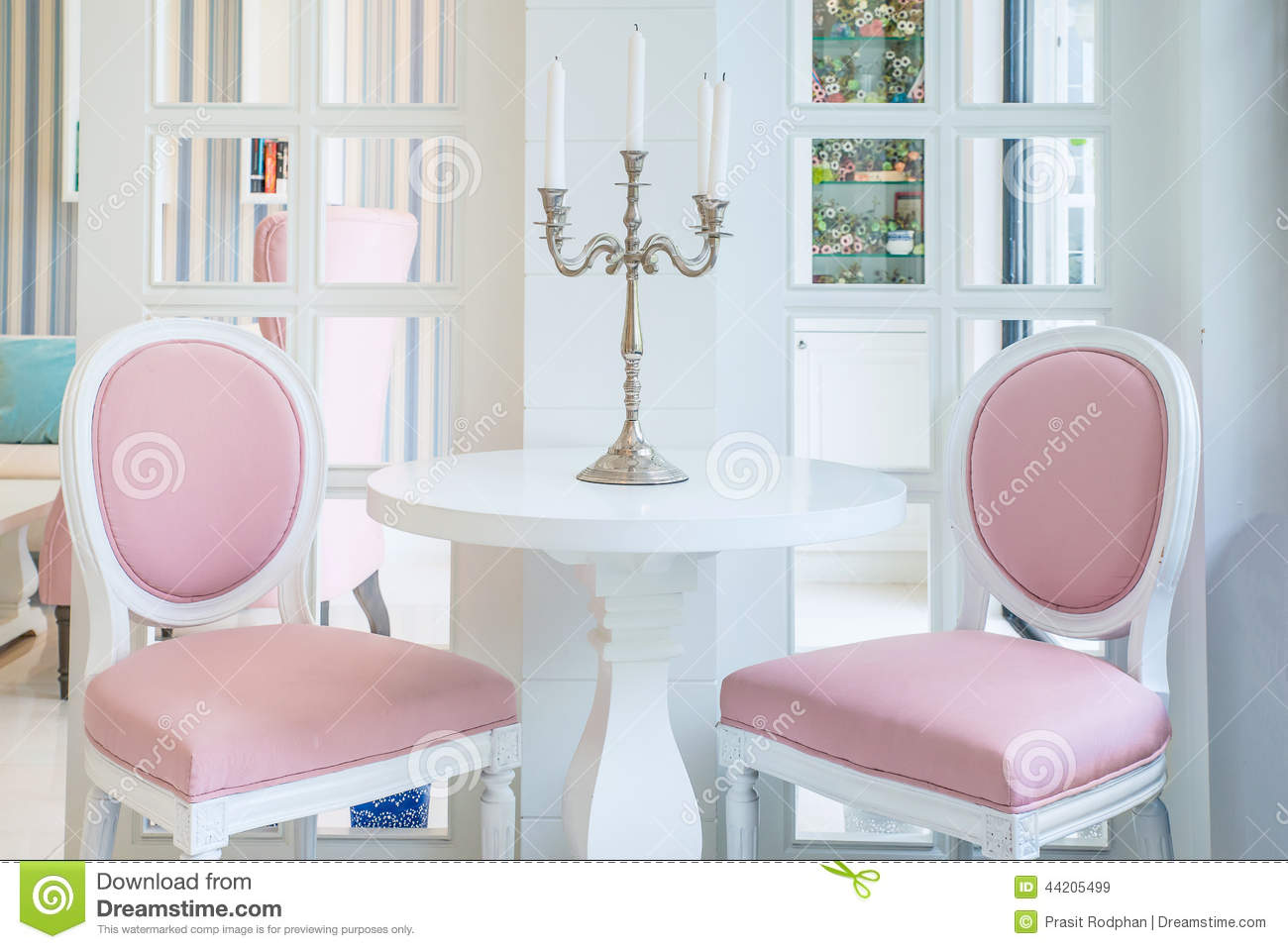 White Table And Pink Chair With Candle On Table In Living Room Stock