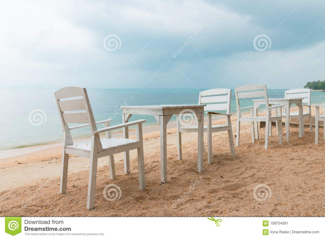 Romantic cafe with white tables and chairs on the sea shore