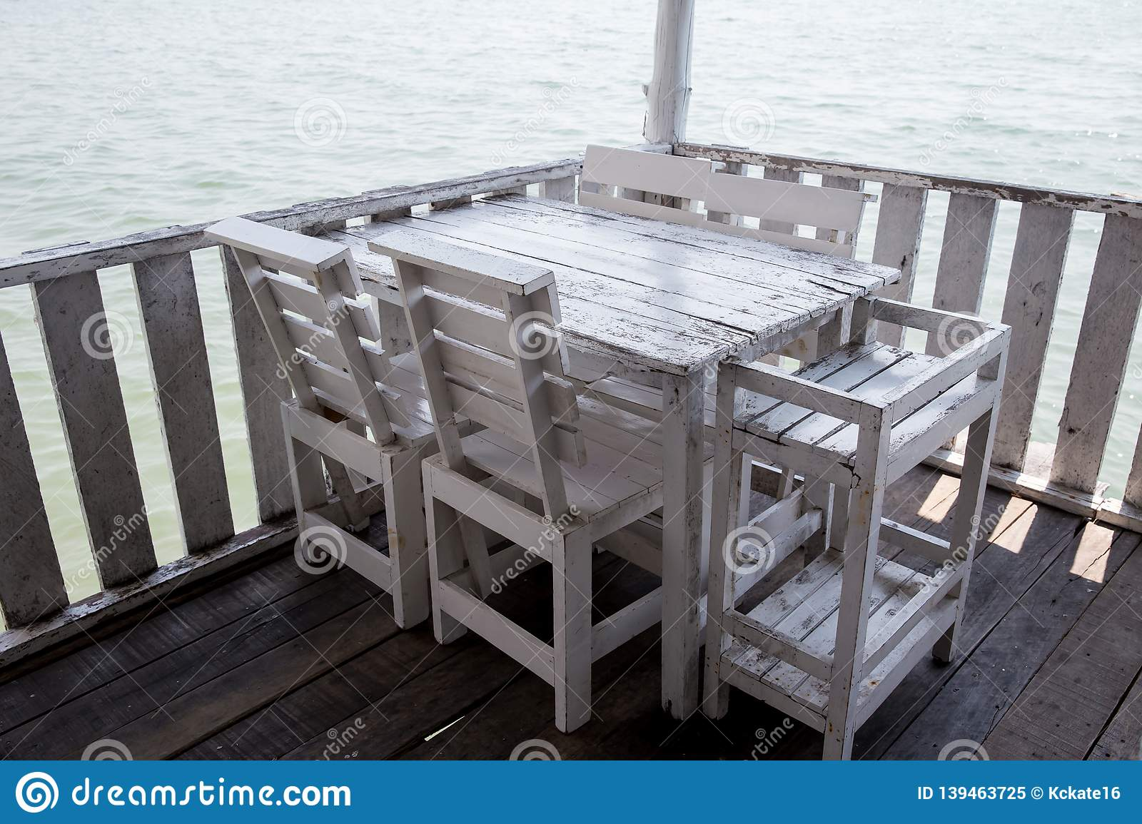 White tables and chairs in restaurant. empty rattan furniture coffee set table chair at wooden floor sea front by the sea.