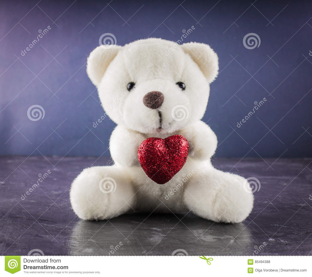 White teddy bear with love letter on red heart gray background. Say i you for valentine `s day concept.