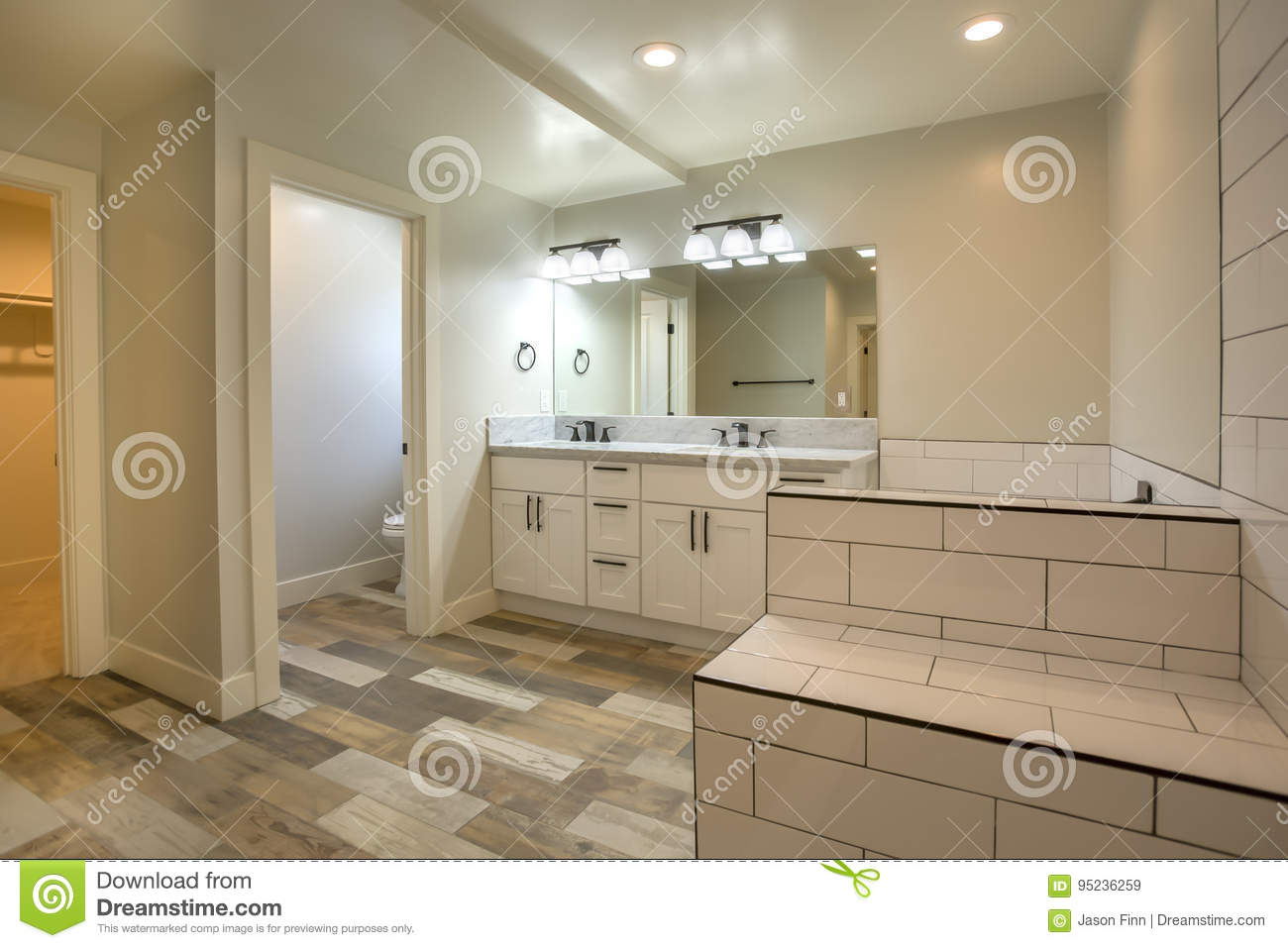 White tile and dark wood floors in open clean bathroom model home san diego southern california