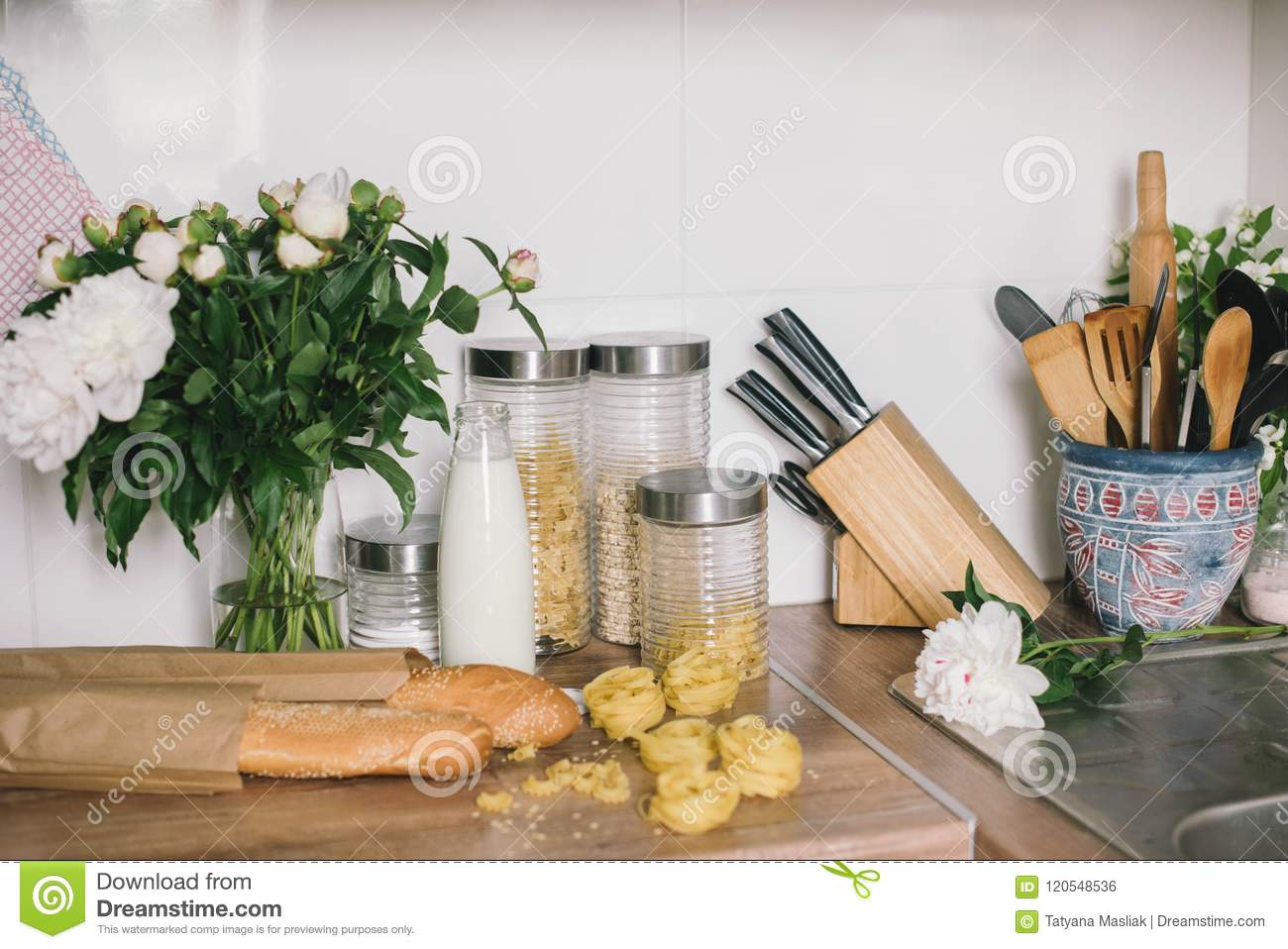 White tiles wall modern kitchen with chopping board,flowers,knifes,pasta,bread.