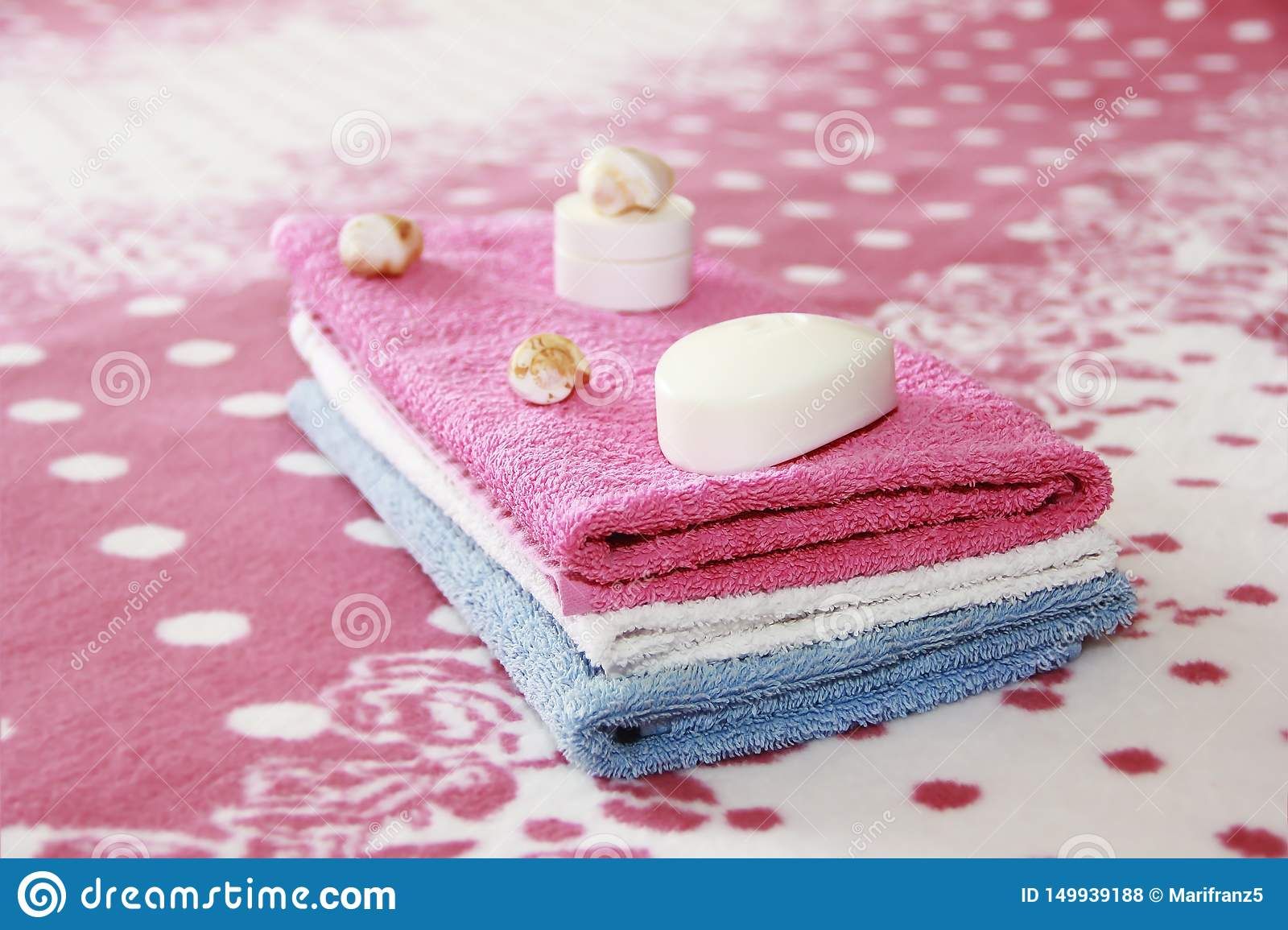 White toilet soap and decor against the background of pink terry towels