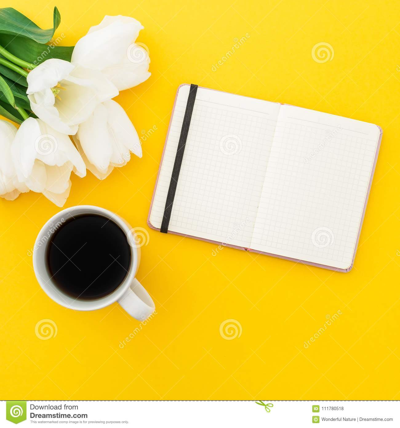 White tulips, notebook with mug of coffee on yellow background. Flat lay, top view.