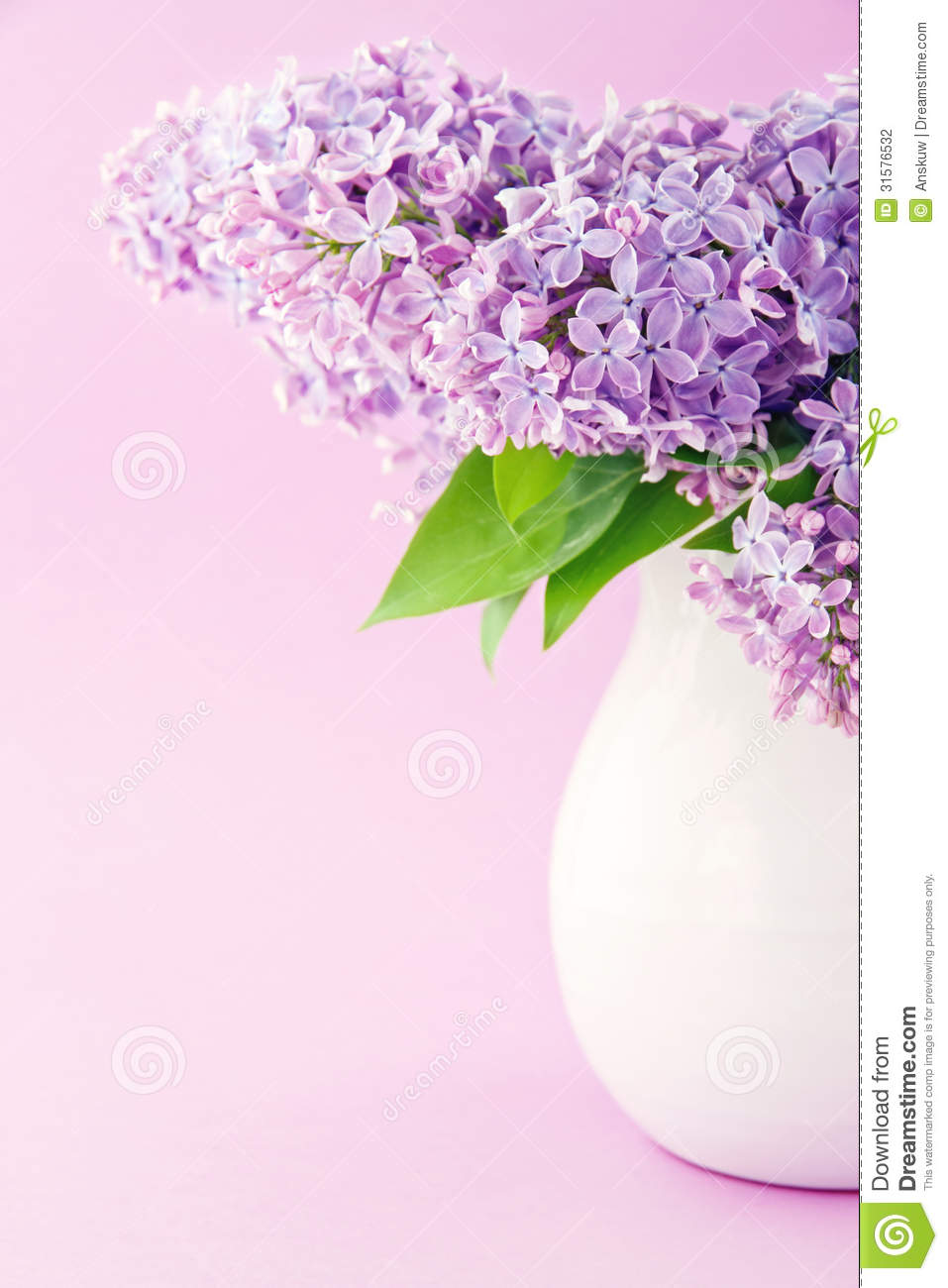 White vase with a bouquet of purple lilac spring flowers.
