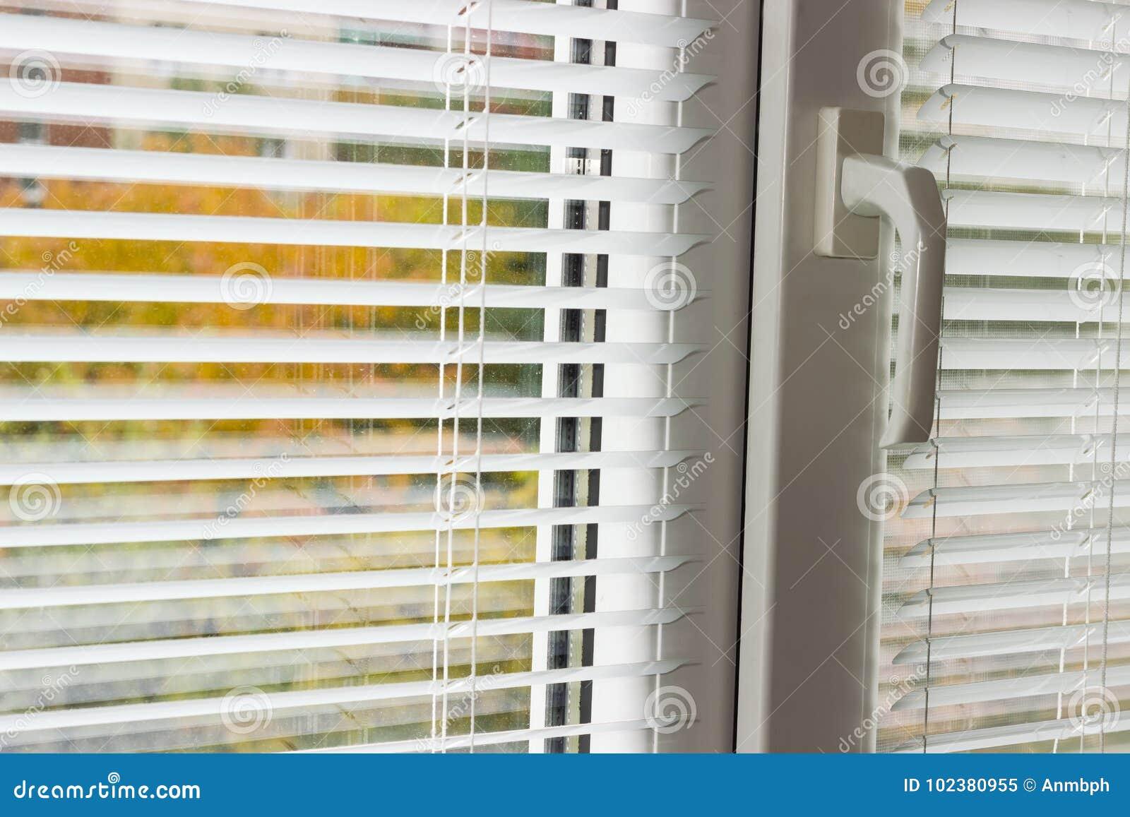 white venetian blinds on a modern plastic window stock. Black Bedroom Furniture Sets. Home Design Ideas