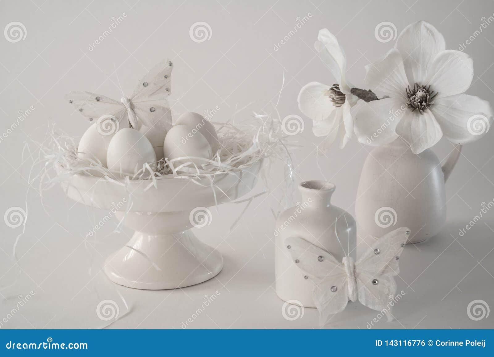 White vintage Easter scene, cake stand with eggs, vases, flowers, against white background