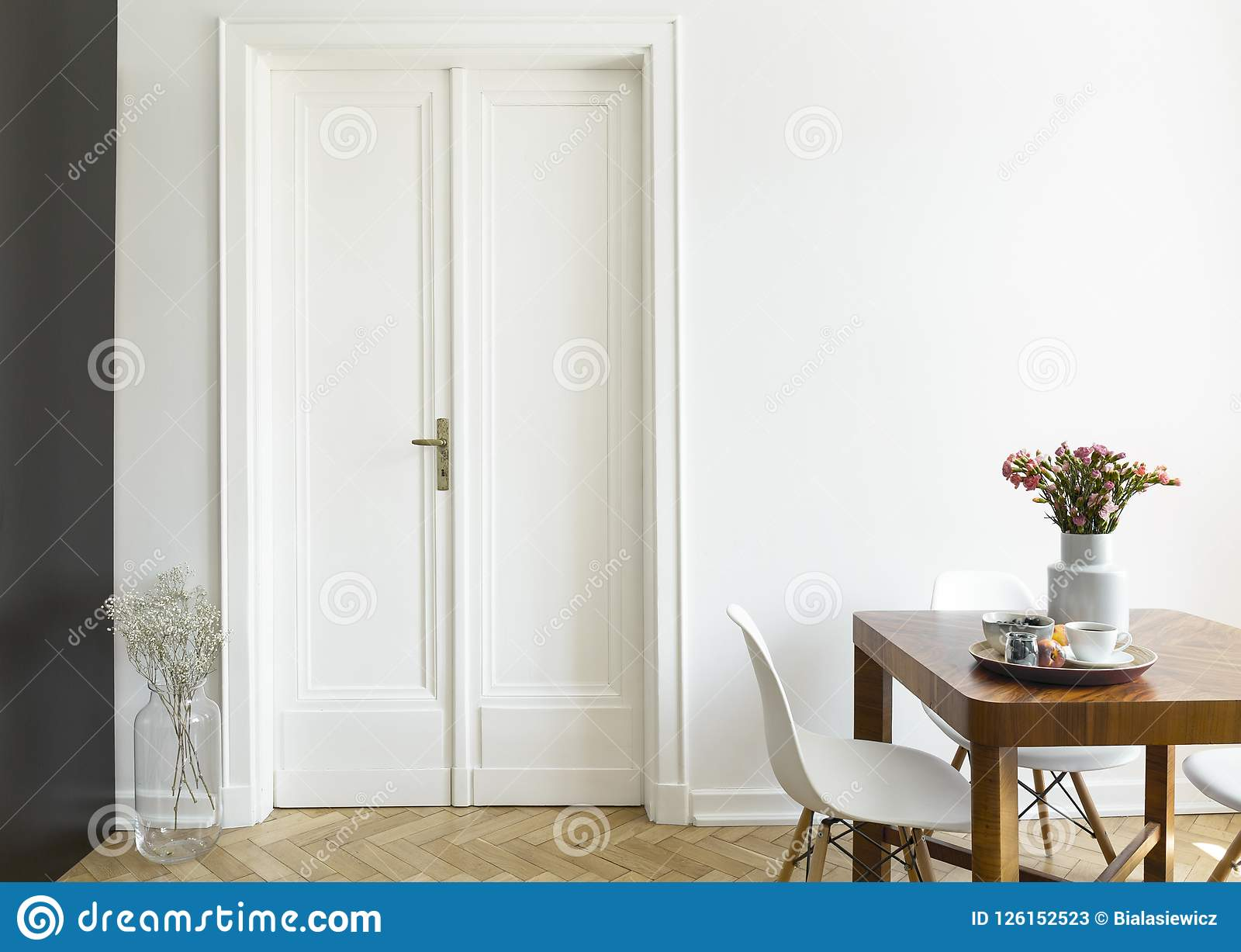 A White Wall With Double Door Next To Wooden Breakfast Table And Chairs In