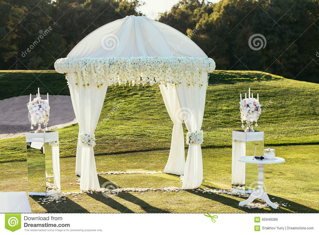 white wedding arch with flowers and candle decoration on sunny royalty free stock images: day orchid decor