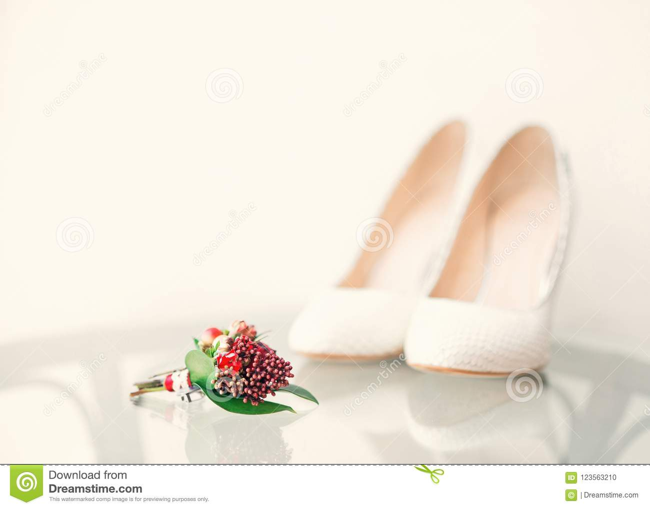 White wedding bride`s shoes and groom`s bouquet in the foregroun
