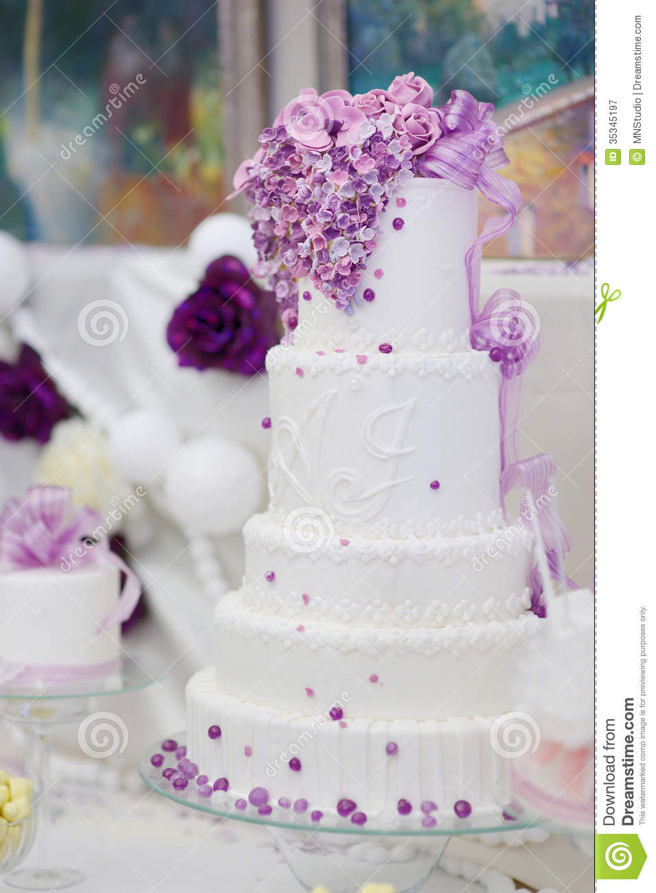 White Wedding Cake Decorated With Purple Flowers Stock Image