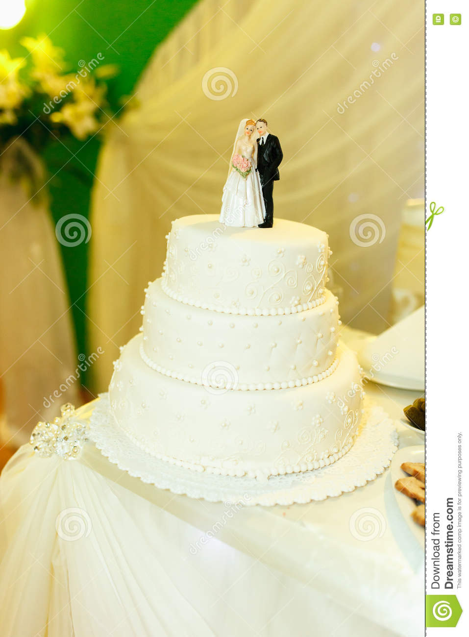 White Wedding Cake With Figures Of Newlyweds On The Top Stock Photo ...