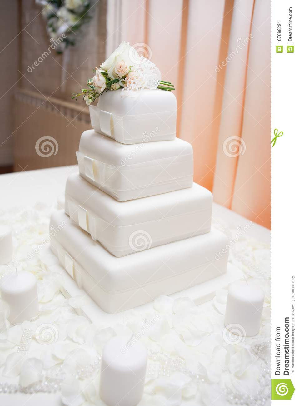 White Wedding Cake With Flowers Decorating The Top And Candles Stock