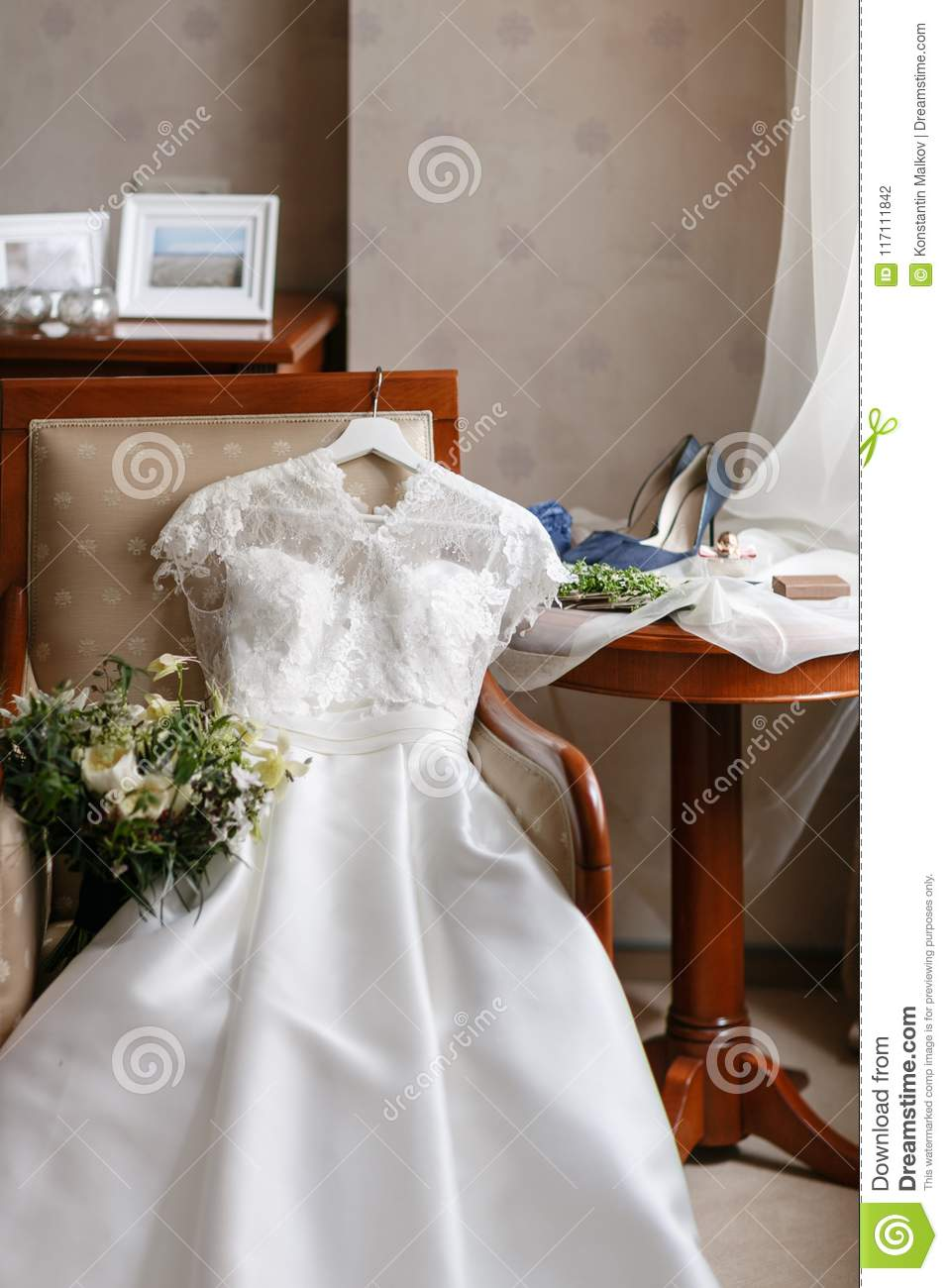 White Wedding Dress With Lace Lying On The Chair Bouquet