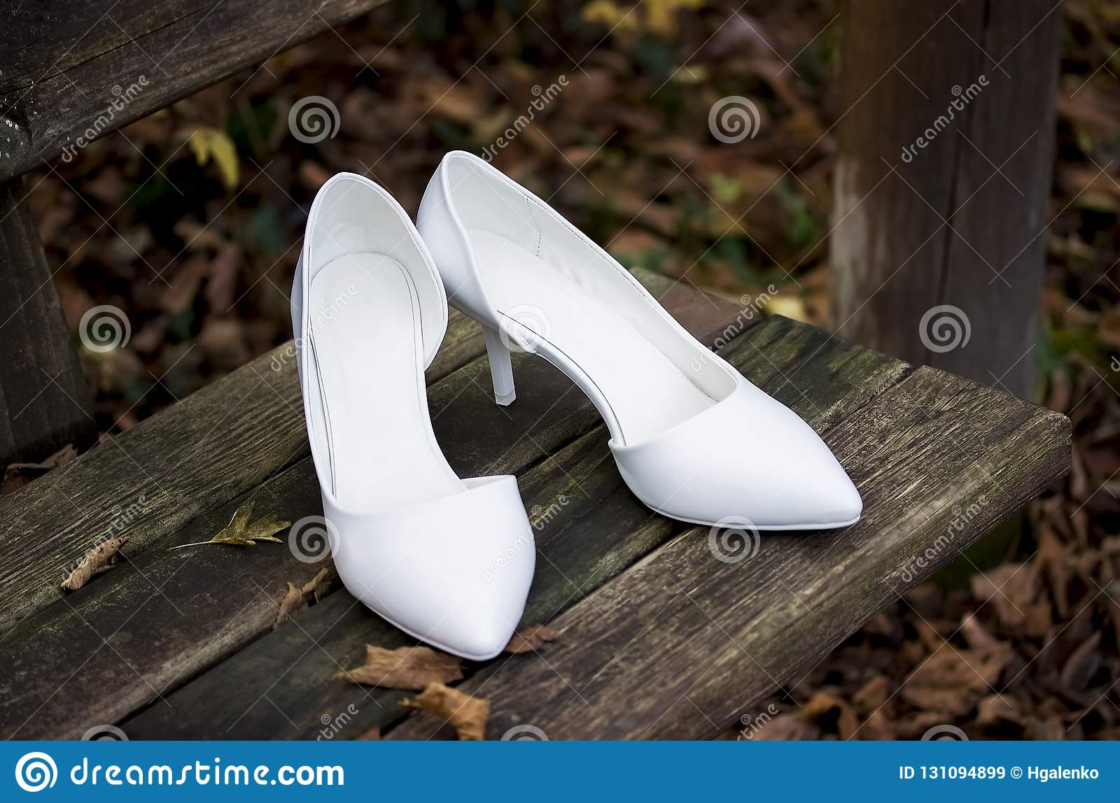 White wedding shoes with autumn foliage on wooden bench.