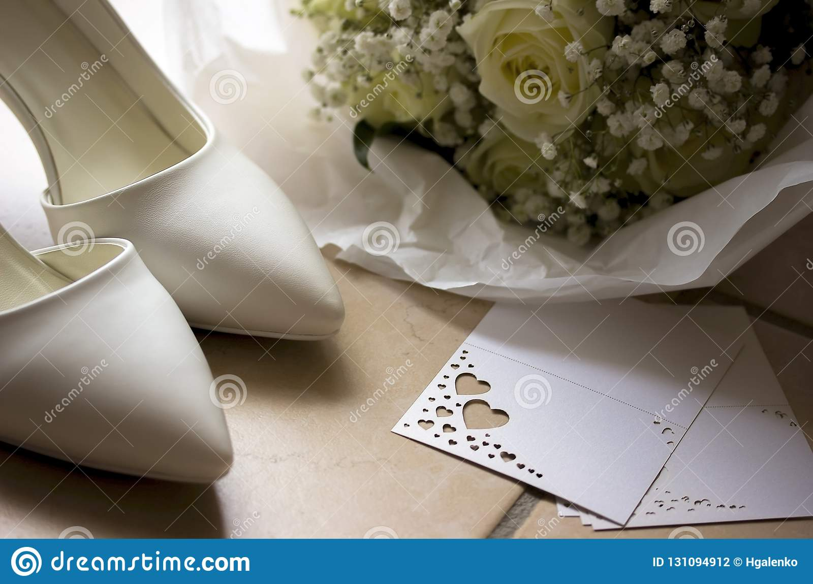 White wedding shoes with bouquet and card.