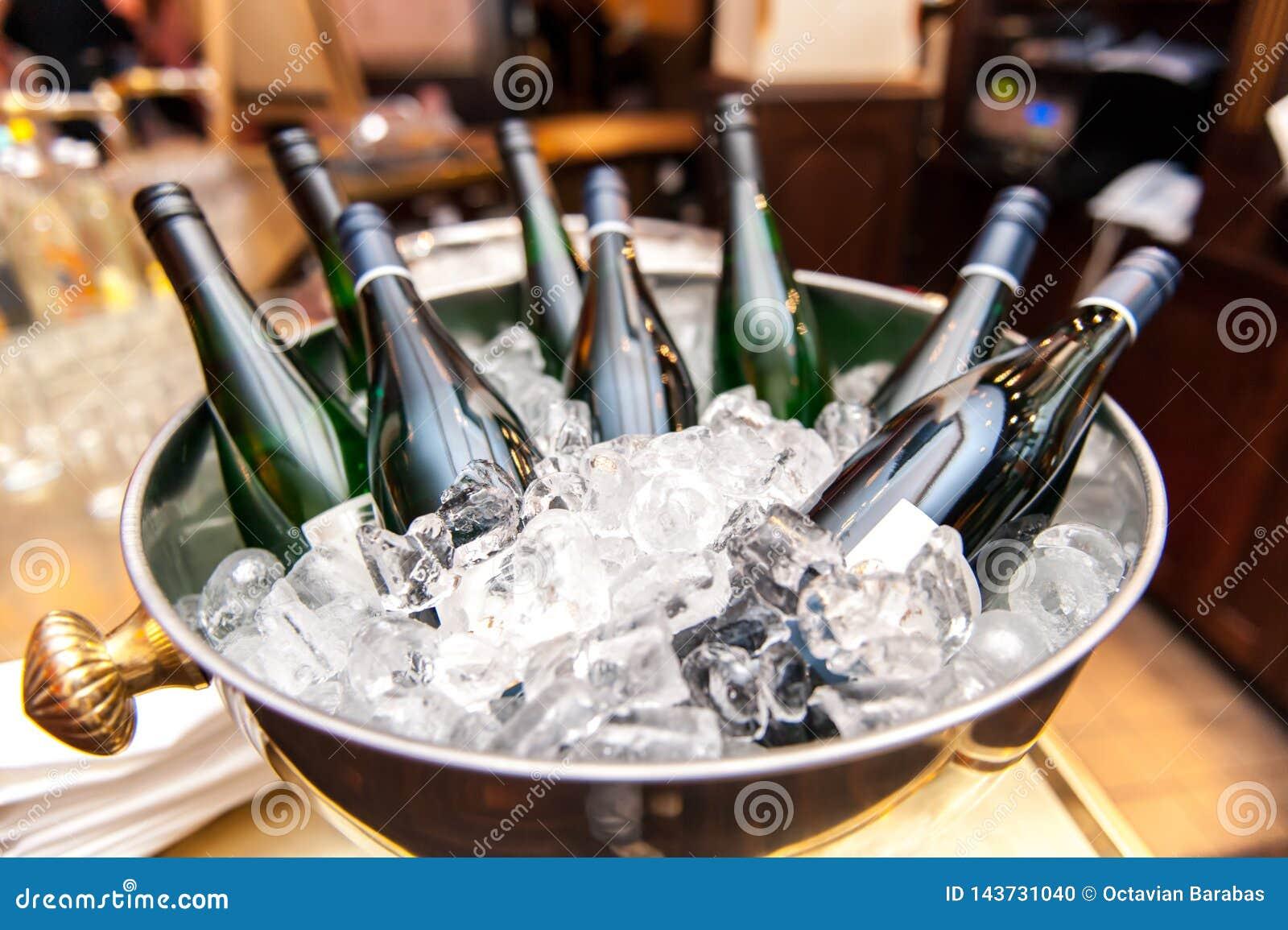 White wine bottles in bowl of ice