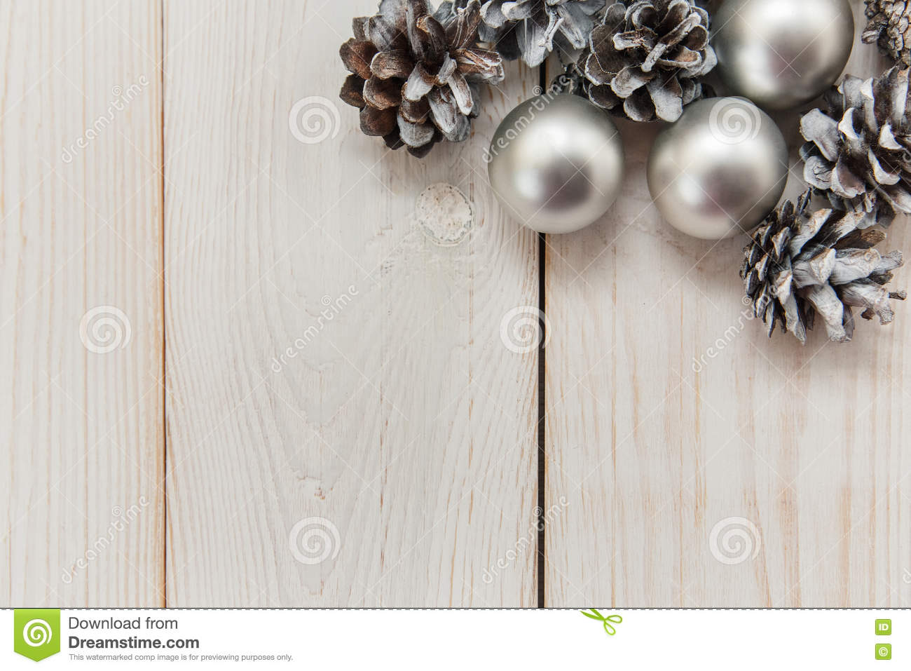 White winter cones on the wooden table with silver balls.Christmas background