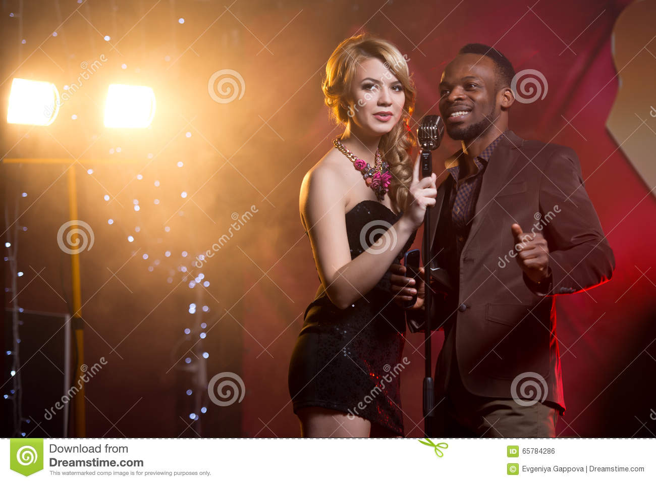 White Woman And Black Man Singing Into A Microphone At The Bar, Couple Singing Stock -7572