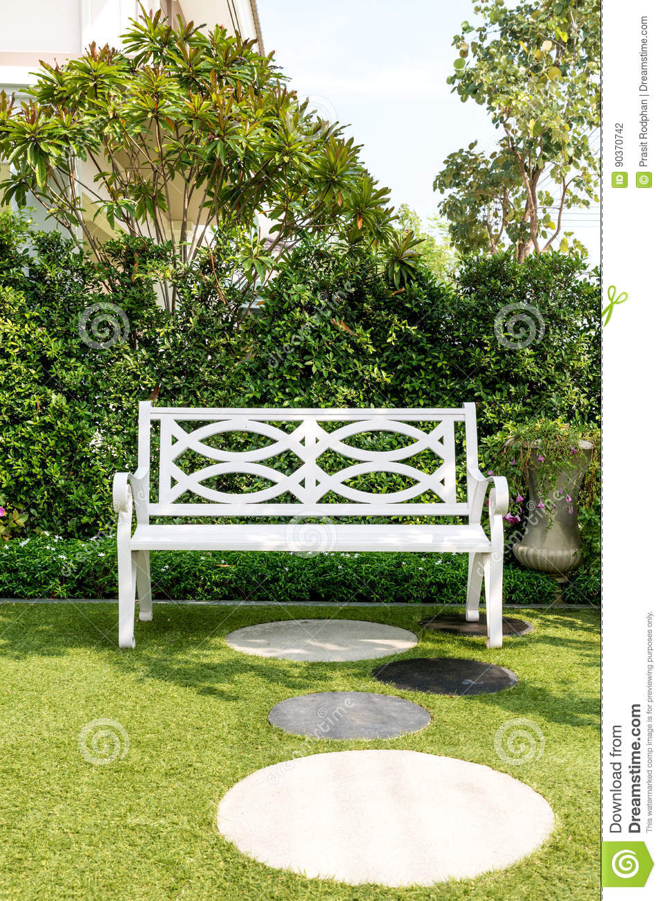 White Wood Bench Chair With Bush Background In Garden At