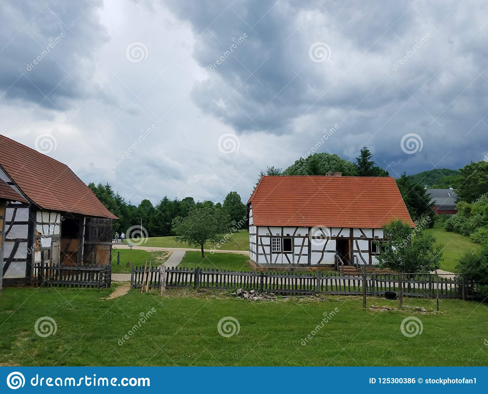 White Wood Building With Red Or Orange Shingle Roof And Green