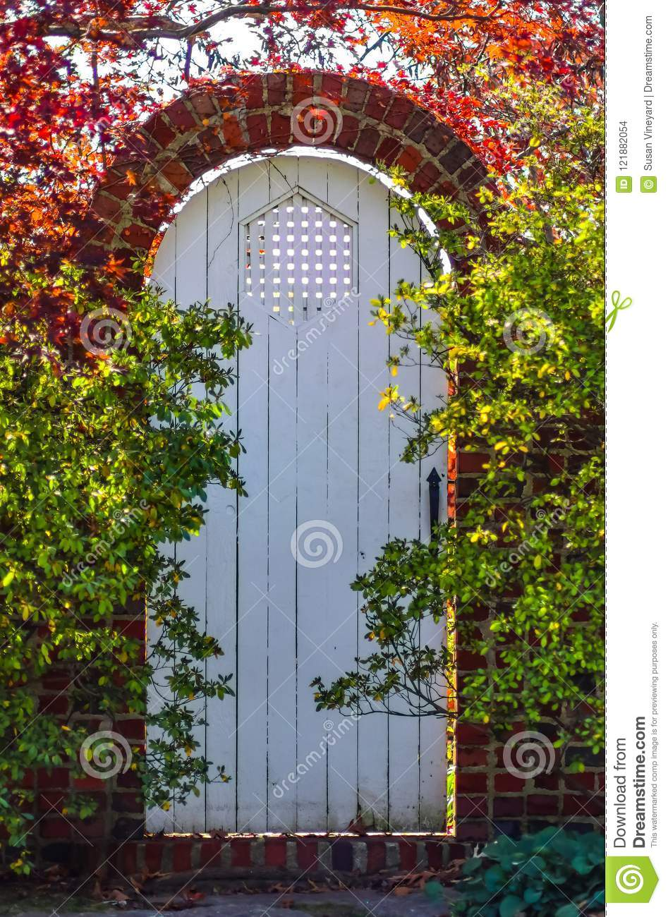 white wooden arched garden gate in autumn in brick wall surrounded