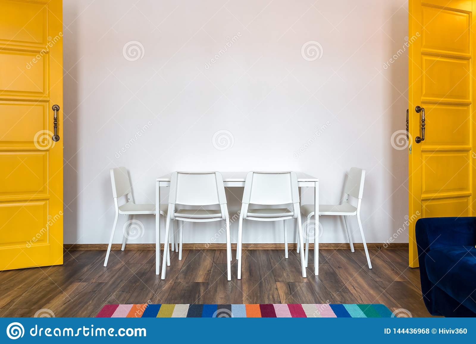 White wooden chairs with a table against the background of a white wall in the interior with yellow doors