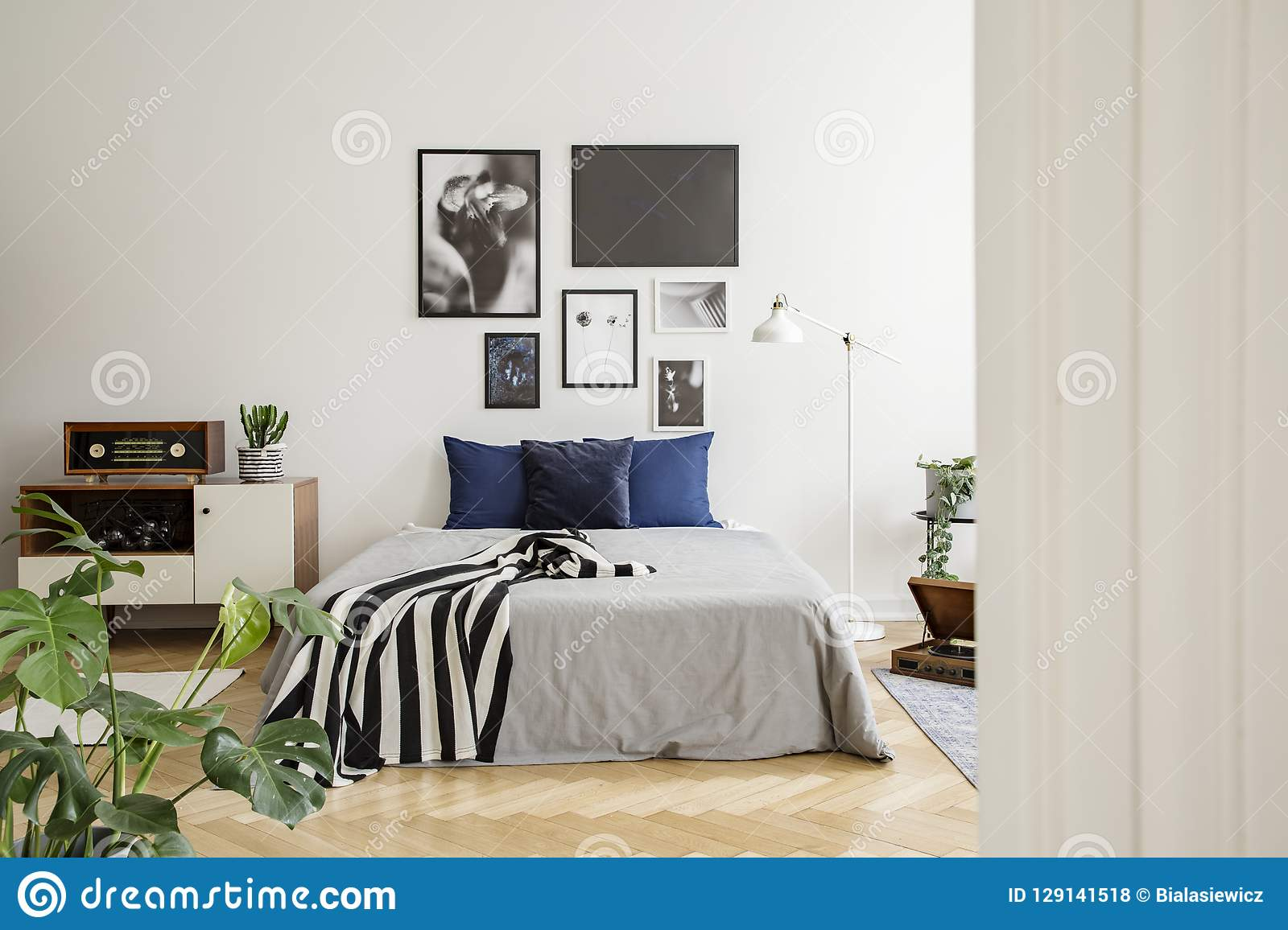 White wooden commode next to bed with dark blue pillows, grey duvet and striped black and white blanket in bedroom