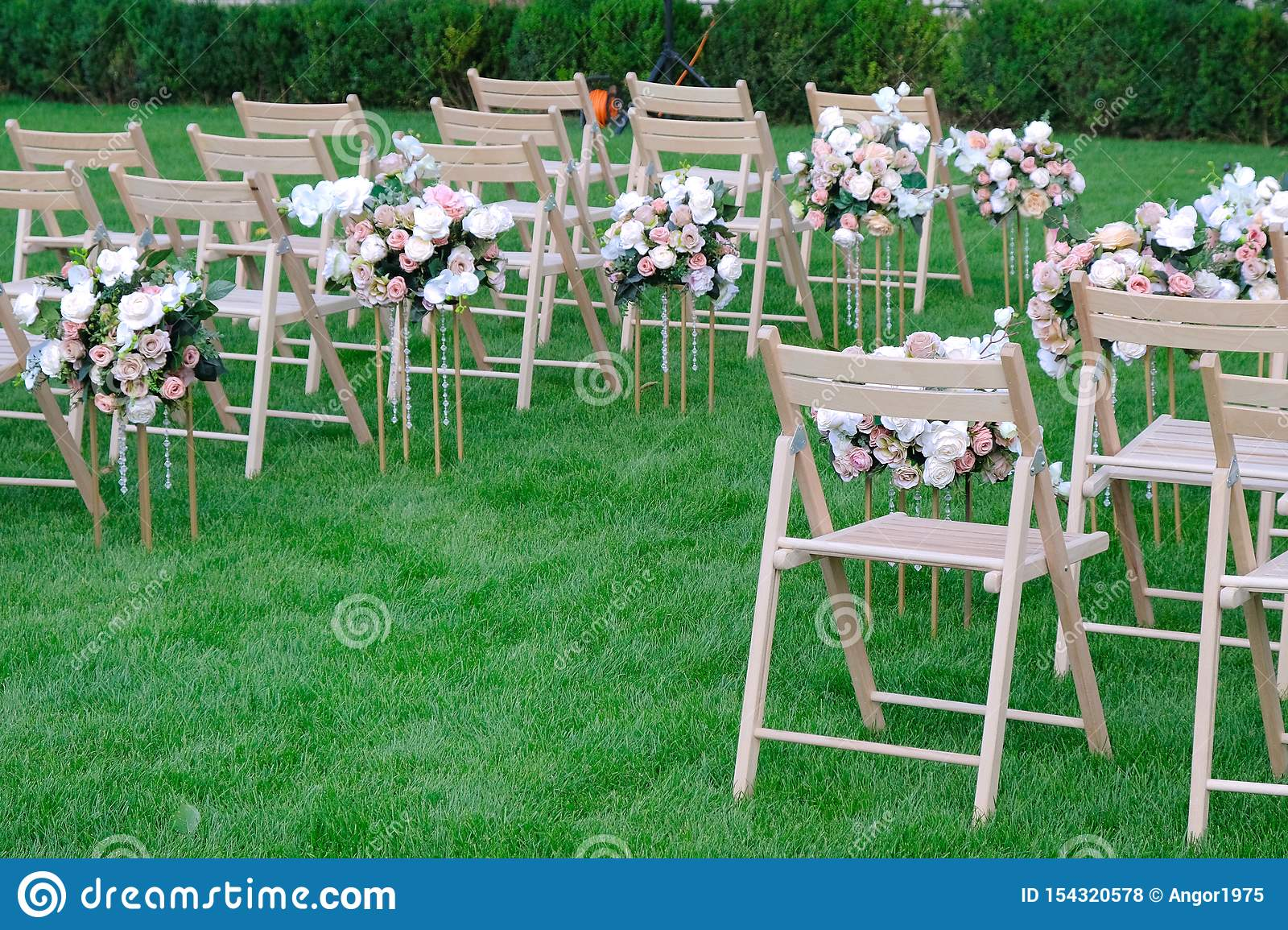 White Wooden Empty Chairs In A Row And Flowers Bouquets On Green Grass Wedding Ceremony Decorations Stock Photo Image Of Bright Furniture 154320578