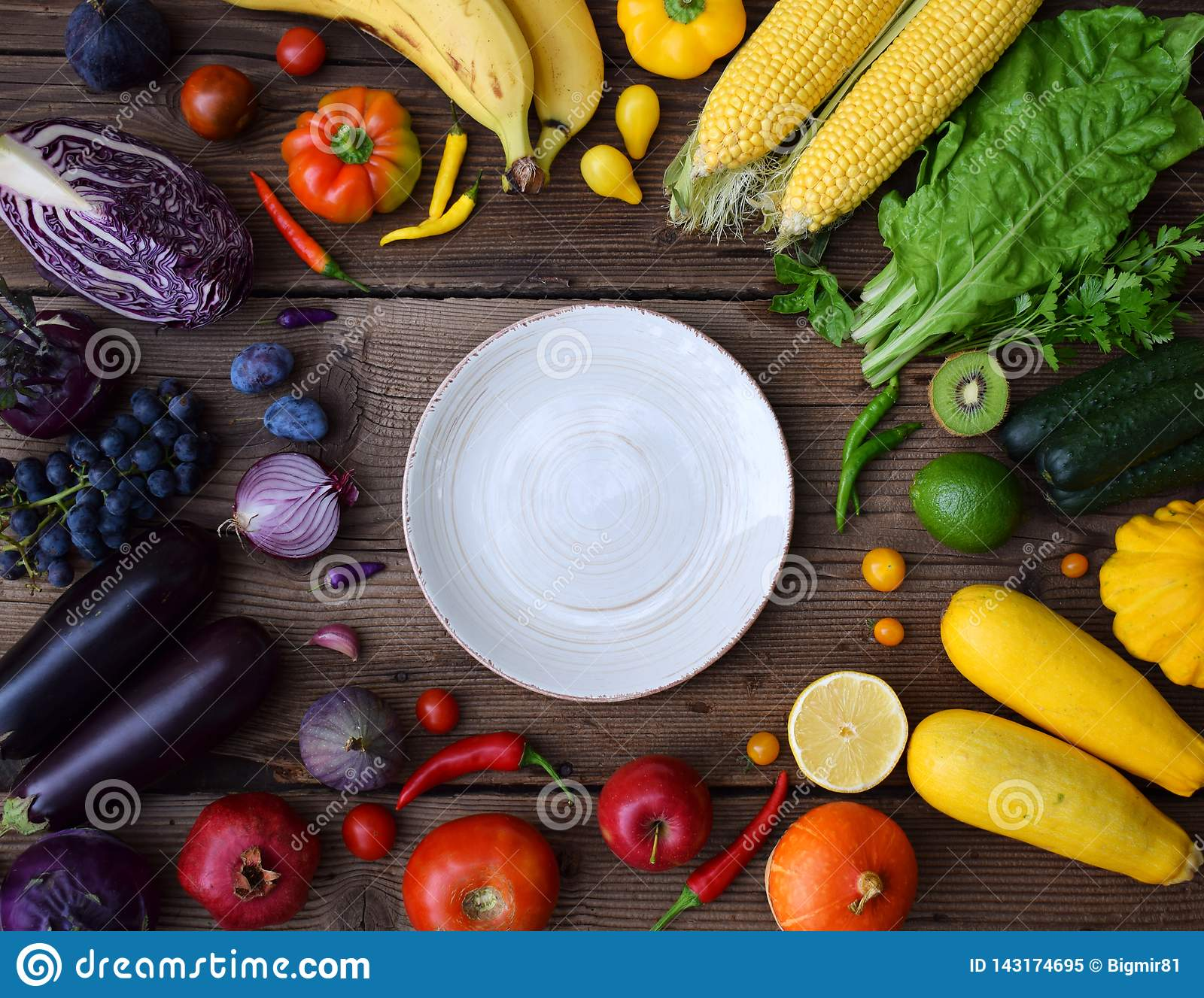 White, yellow, green, orange, red, purple fruits and vegetables on wooden background.  Healthy food. Multicolored raw food and