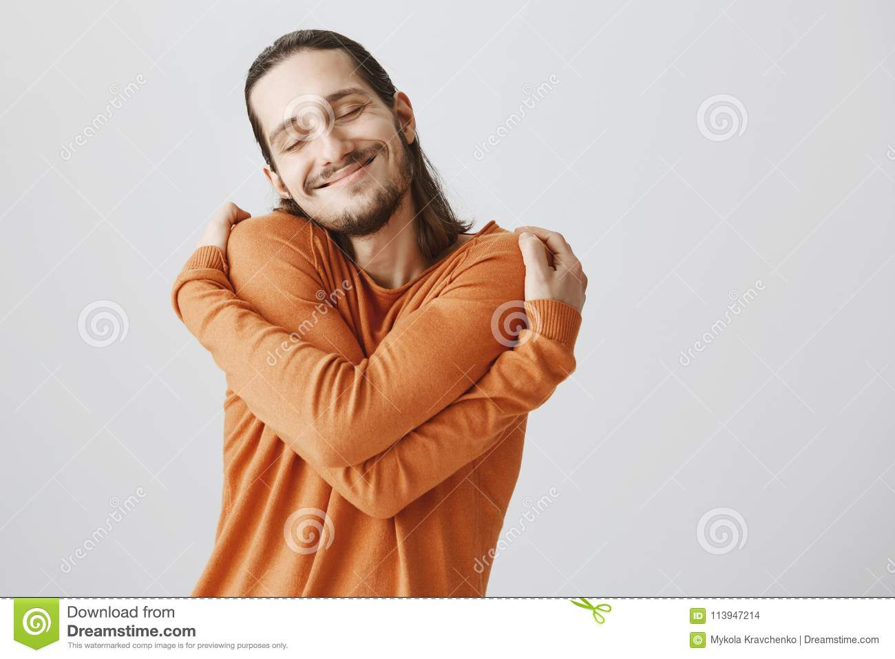 Who need girlfriends if you can hug yourself. Funny playful european guy with long hair and beard cuddling himself and