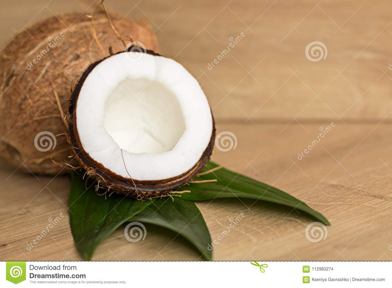 Whole and Broken Coconuts on a Brown Background
