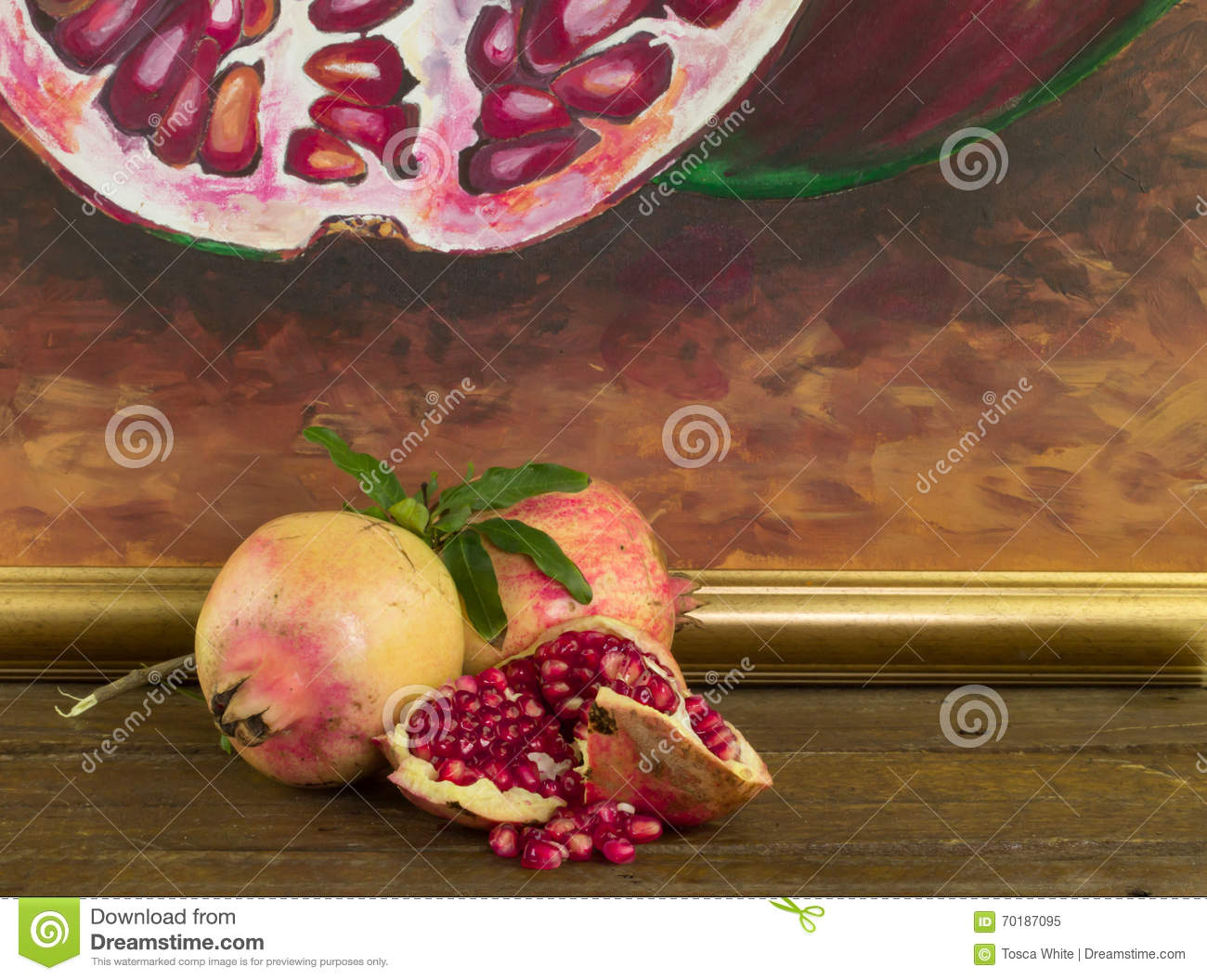 Whole and broken pomegranate on wood