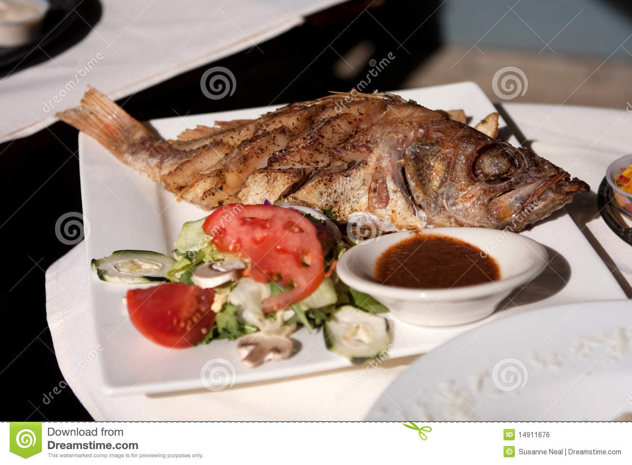 Whole cooked fish and salad