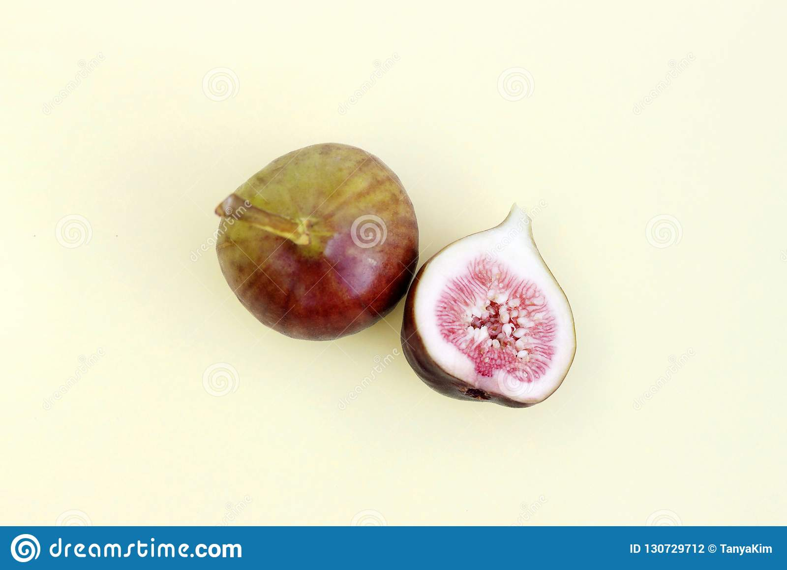 Whole and cut figs close-up, yellow background, top view