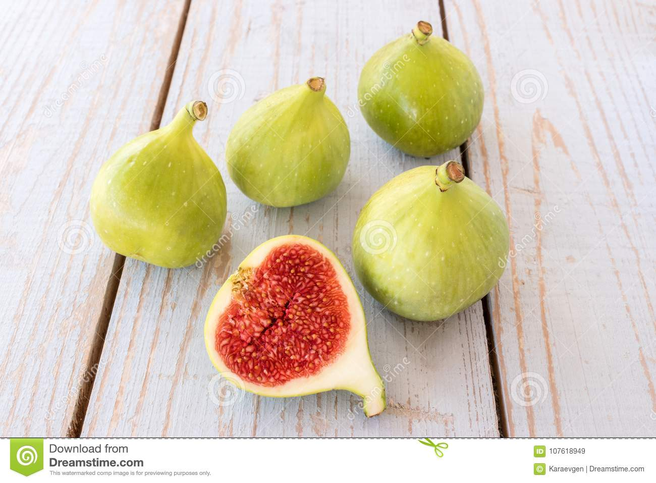 Whole Figs And One Fig Sliced In Half On Top Of A Garden