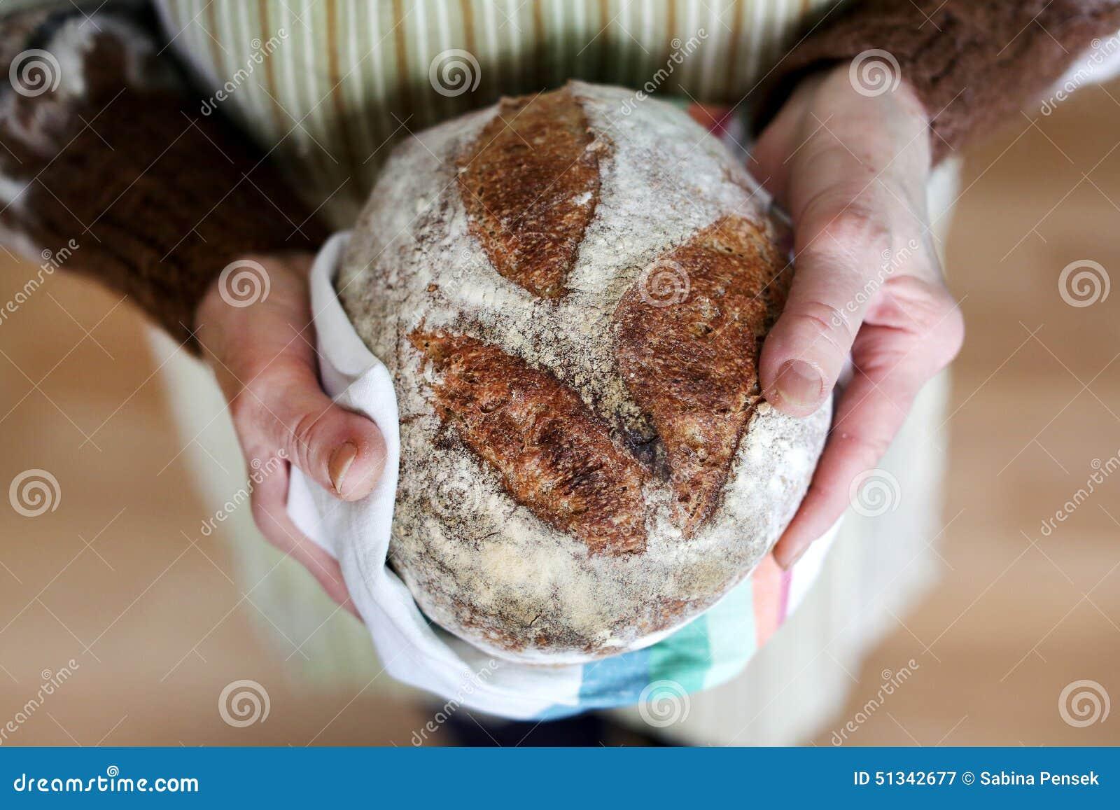 Whole-grain artisanaal broodbrood in grootmoederhanden, het bakken