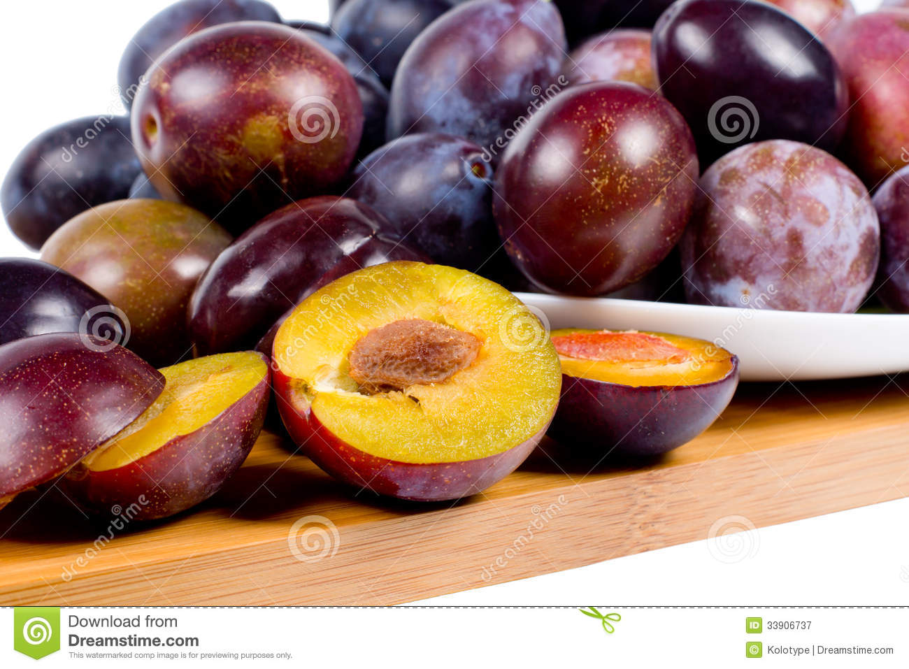 Whole and halved fresh red plums