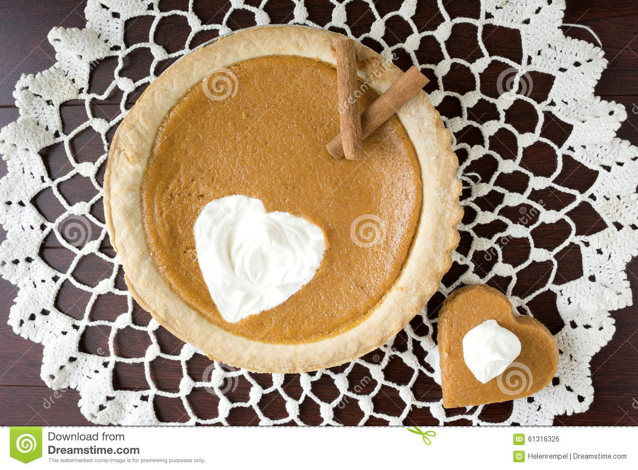 whole pumpkin pie with a heart shape cut out with piece