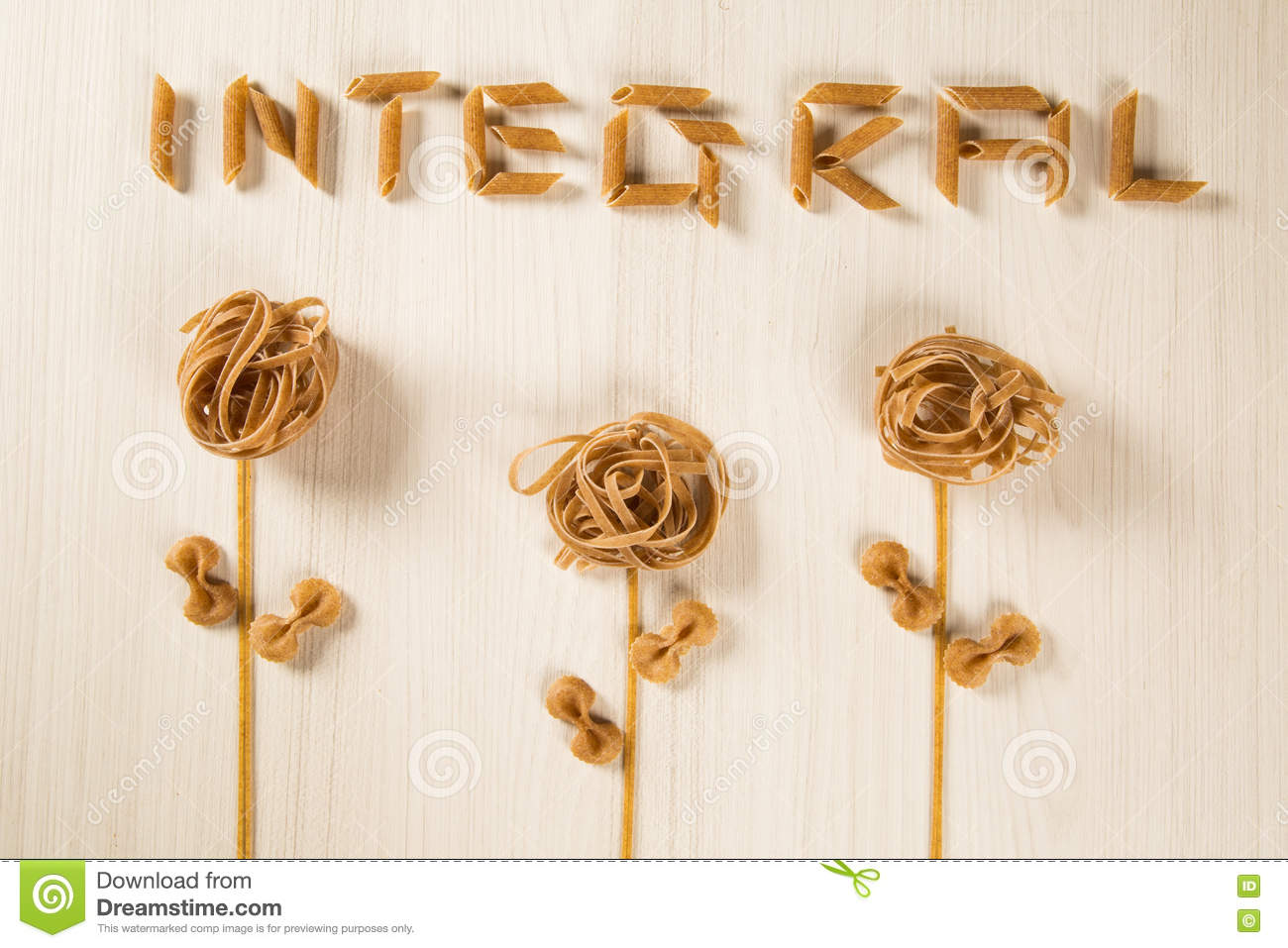 Whole-shaped integral pasta with flowers on a white wooden table