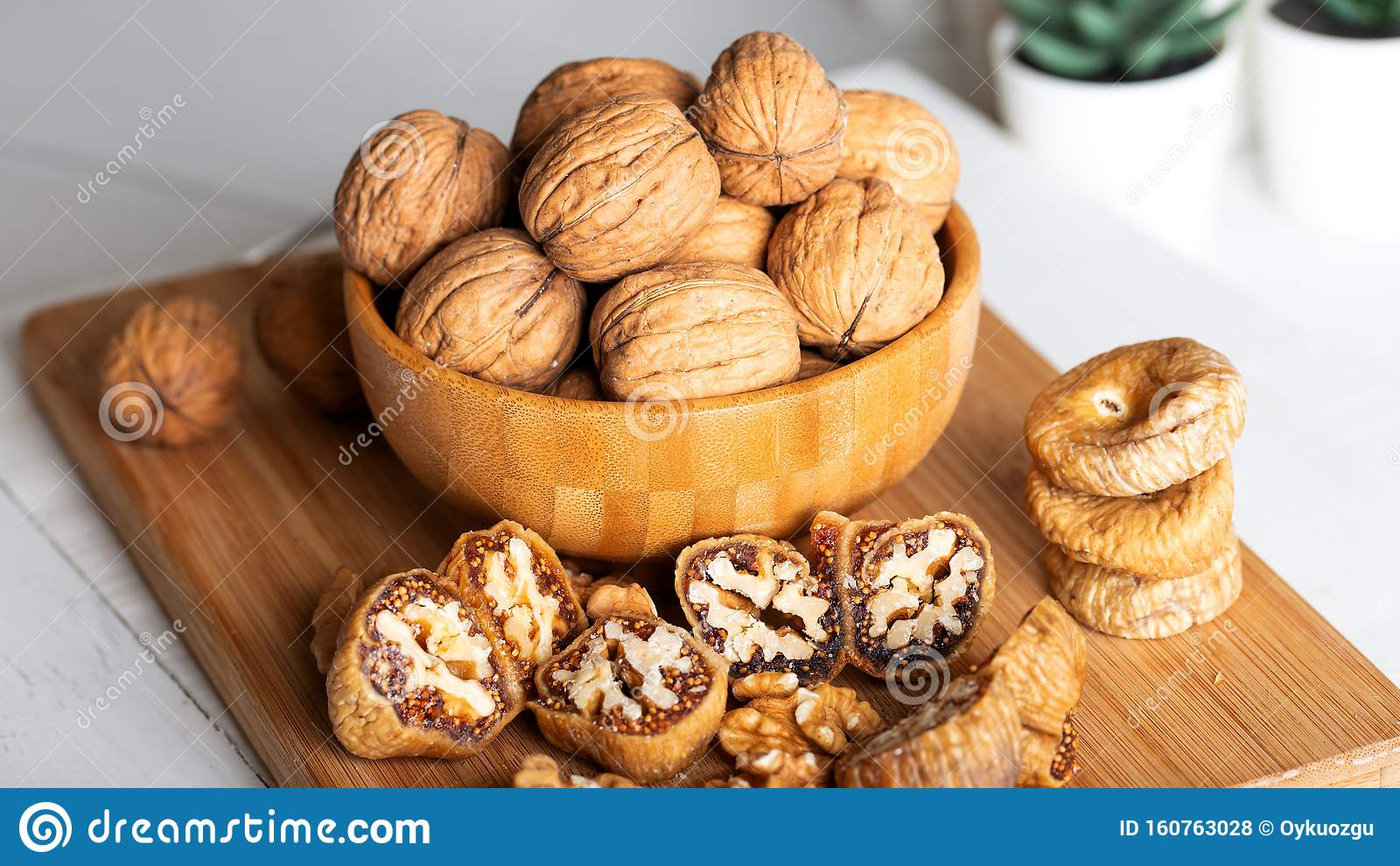 Whole Walnuts In Bowl. Dried Figs With Walnuts On Wooden Background Stock Photo