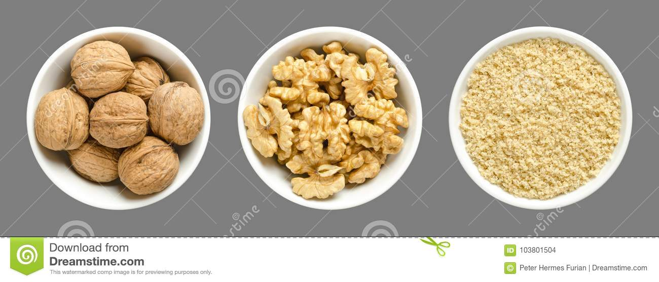 Whole, walnuts, kernel halves and ground walnuts in white bowls on gray background