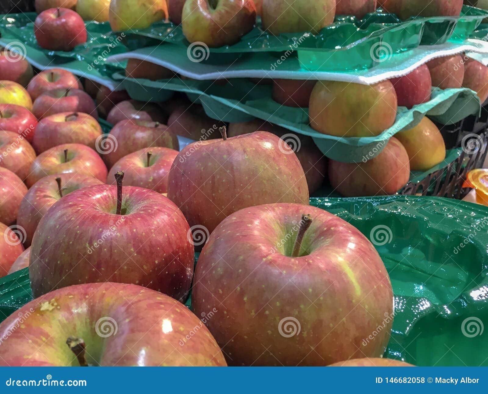 Wiązka czerwoni Fuji jabłka w jabłczanych tacach przy supermarketem