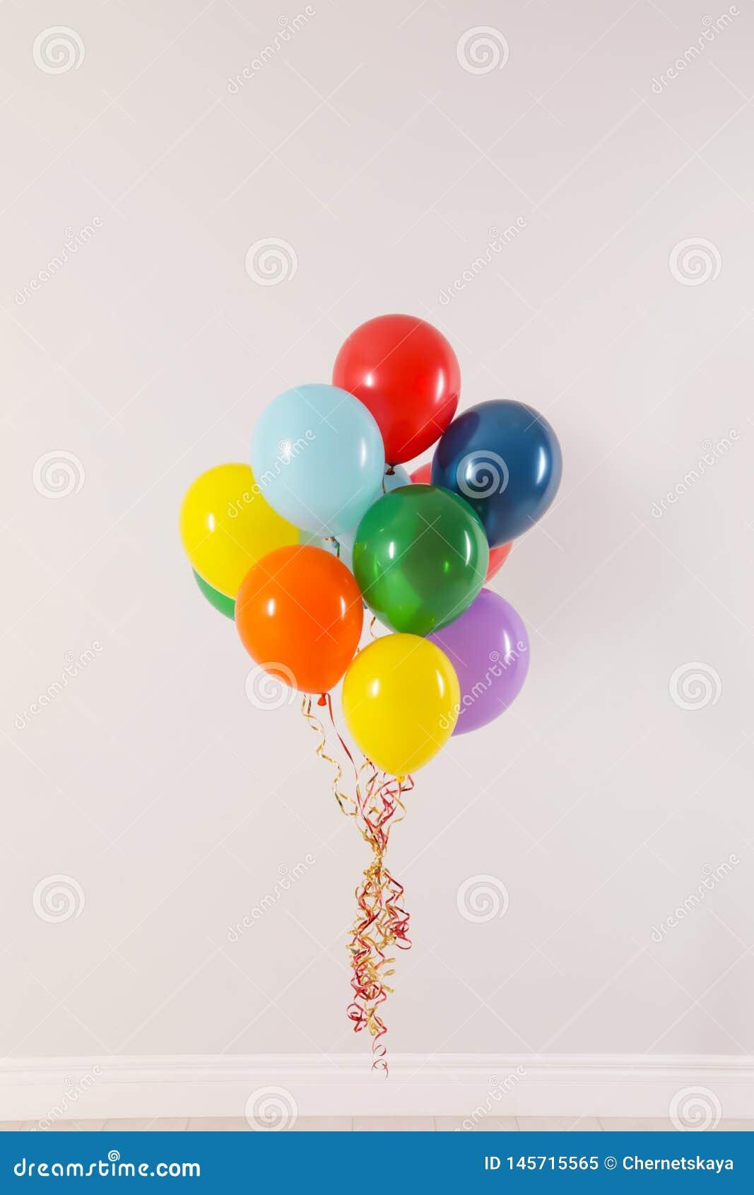Wiązka jaskrawi balony przeciw światło ścianie
