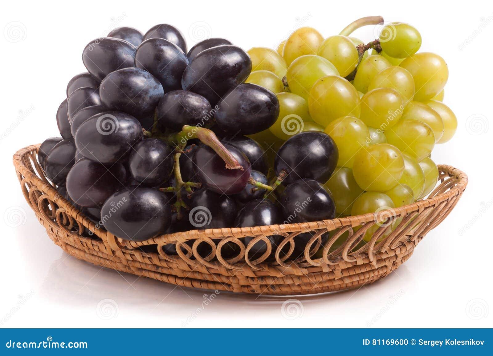 Wiązka zieleni i błękitni winogrona w łozinowym koszu odizolowywającym na białym tle